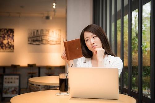 手帳を見て悩む女性