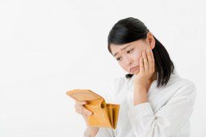 お財布を見て悩む女性